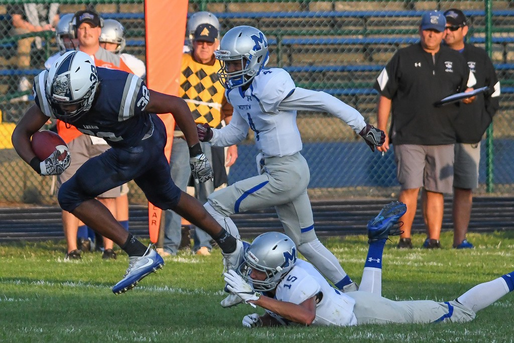 . Eric Bonzar�The Morning Journal<br> Lorain running back Savon Chavis (32) breaks a shoestring tackle by Midview\'s Nick Crum (15) in the first quarter, Aug. 25, 2017.