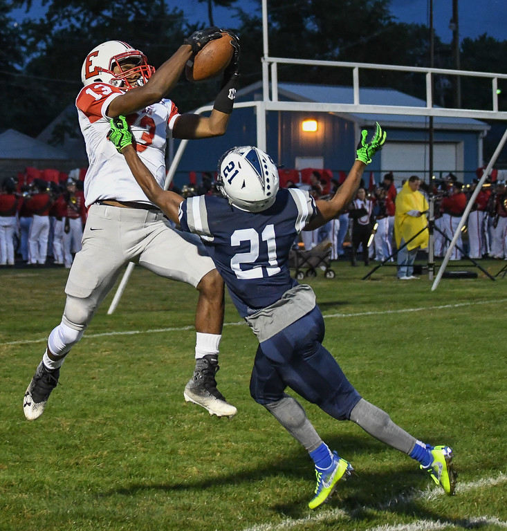 . Eric Bonzar�The Morning Journal<br> Elyria\'s Deviian Williams (13) pulls in a touchdown over Lorain\'s Zion Cross (21), Sept. 7, 2017.