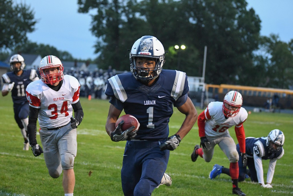 . Eric Bonzar�The Morning Journal<br> Lorain Titans wide receiver Tyshawn Lighty (1) shreds off 39 yards against the Elyria Pioneers, Sept. 7, 2017.