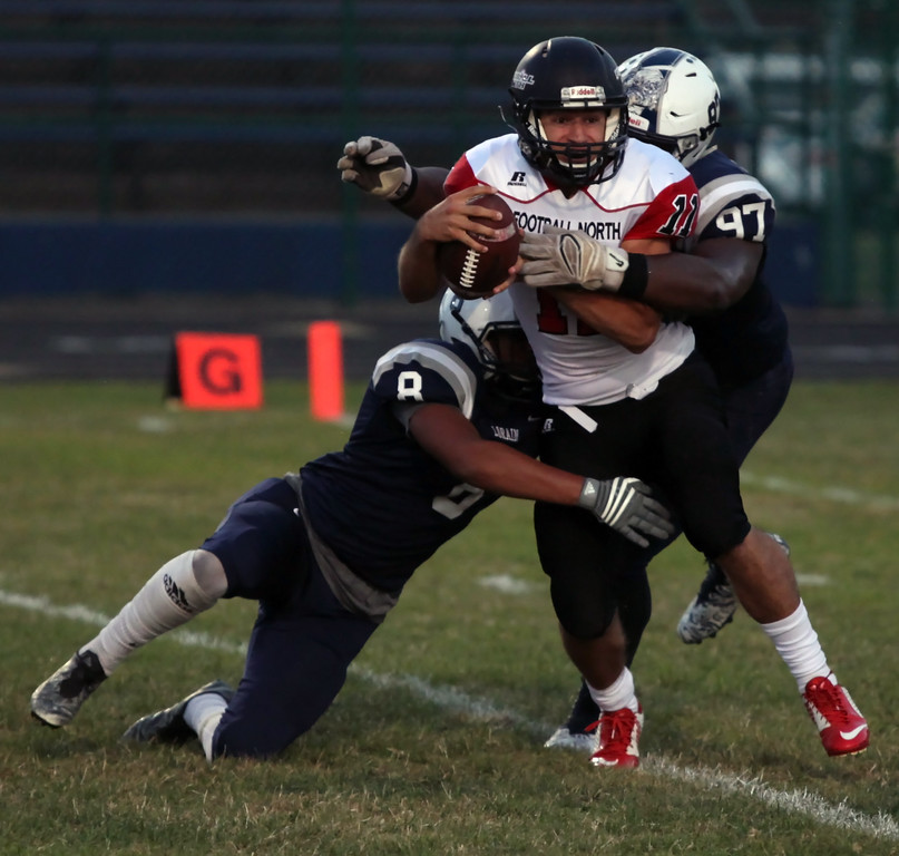 . Randy Meyers - The Morning Journal<br> Lorain\'s Malik McCall and Antonio Wyatt combine on the sack of Clarkson quarterback Nick DeJesus during the first quarter on Sept. 22.