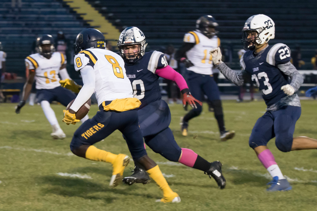 . Jen Forbus - The Morning Journal<br> Warrensville Heights slotback Dyson Giddens (8) tries to gain yardage, but Lorain linebacker Isaiah McDowell and defensive back Jermele Nolen (23) close in on himn Oct. 6.