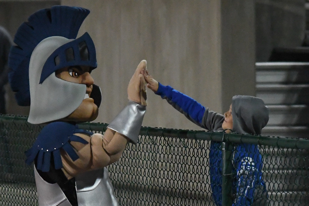 . Eric Bonzar�The Morning Journal<br> A Titans fan gets a high five from Lorain\'s new mascot, Titus, during the team\'s Lake Erie League conference game against Bedford, Oct. 20, 2017. The Titans would lose the road game, 54-48 to the Bearcats.