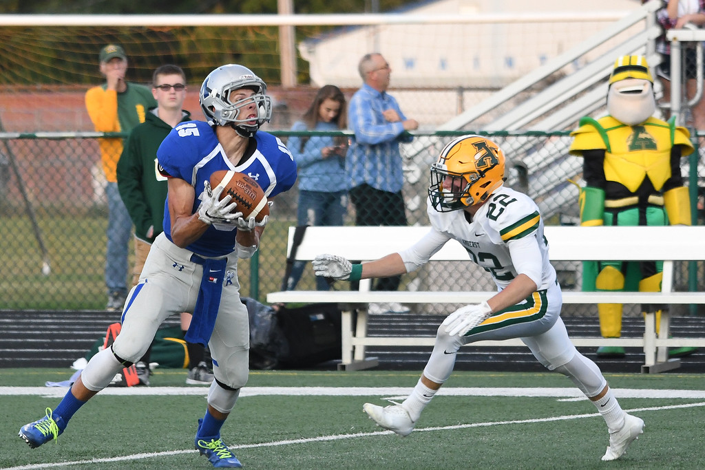 . Eric Bonzar�The Morning Journal<br> Midview\'s Nick Crum (15) fields a punt with Amherst\'s Hunter Park (22) bearing down on him, Sept. 15, 2017.