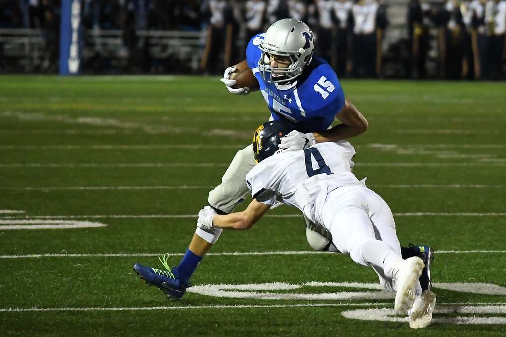 . Eric Bonzar�The Morning Journal<br> Midview wide receiver Nick Crum (15) is hit by Olmsted Falls defensive back Josh Jaeckin (4), Oct. 13, 2017.