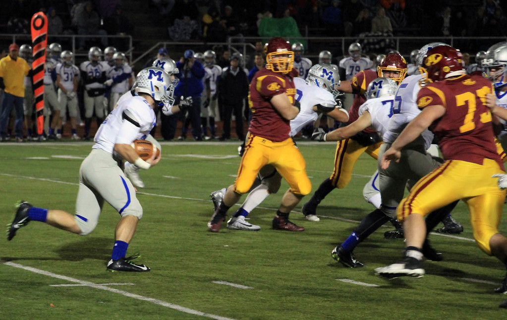 . Nicholas Pfeifer - The Morning Journal<br> Midview\'s Connor Wolfe takes the hand off on the read option and barrels forward for a short gain against Avon Lake on Oct. 27.