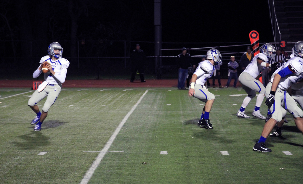 . Nicholas Pfeifer - The Morning Journal<br> Midview\'s Seamus Higley drops back to pass against Avon Lake on Oct. 27.