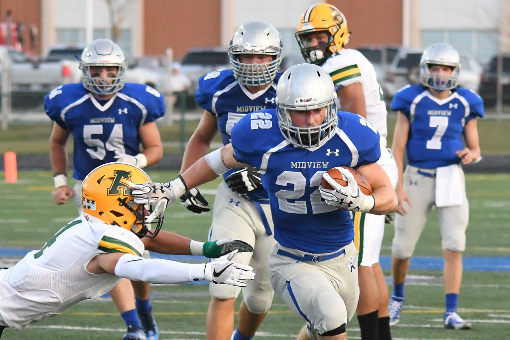 . Eric Bonzar�The Morning Journal<br> Midview running back Connor Wolfe (22) stiff arms his way past Amherst defensive back Hunter Cassidy (4), Sept. 15, 2017.