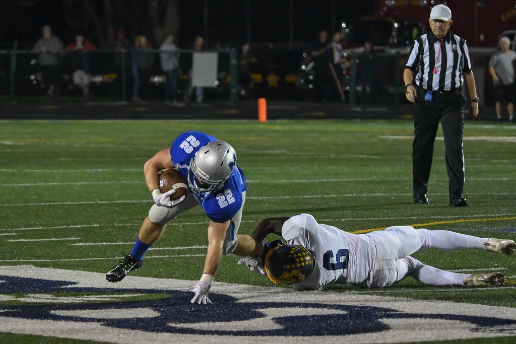 . Eric Bonzar�The Morning Journal<br> Midview running back Connor Wolfe (22) is tripped up by Olmsted Falls\' Michael Howard (6) , Oct. 13, 2017.