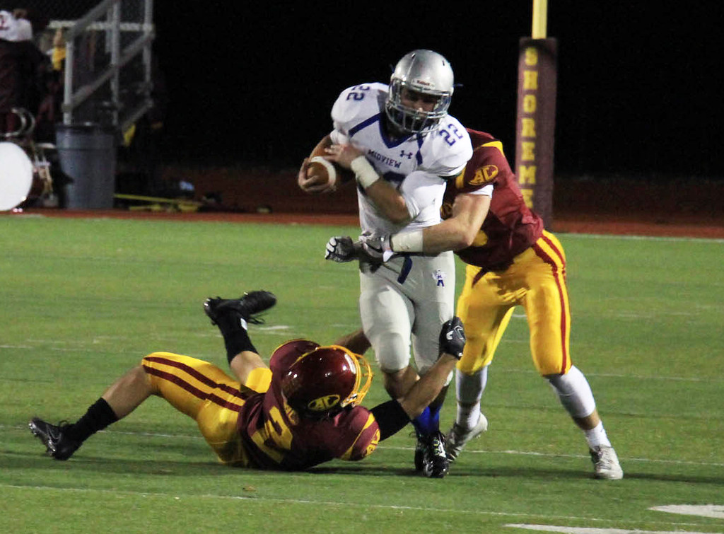 . Nicholas Pfeifer - The Morning Journal<br> Midview\'s Connor Wolfe barrels through two Avon Lake defenders for a big gain on Oct. 27.