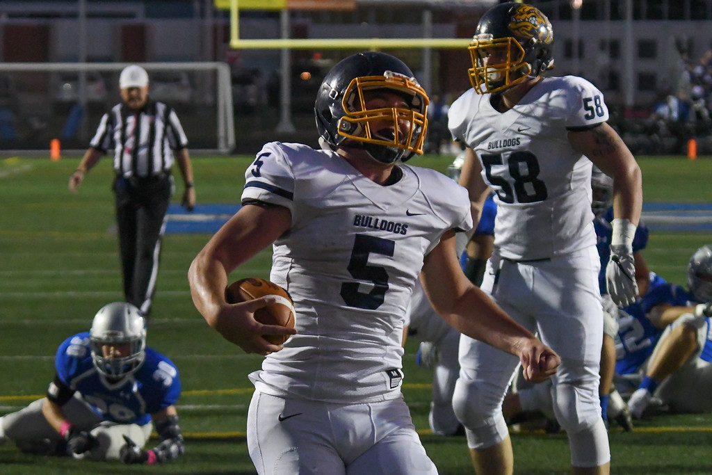 . Eric Bonzar�The Morning Journal<br> Olmsted Falls running back Luke Lombardo (5) clenches his fist after crossing the goal line and giving the Bulldogs their first six points of the night, Oct. 13, 2017. Lombardo had three touchdowns on the night, in his team\'s 41-27 win over the Midview Middies.