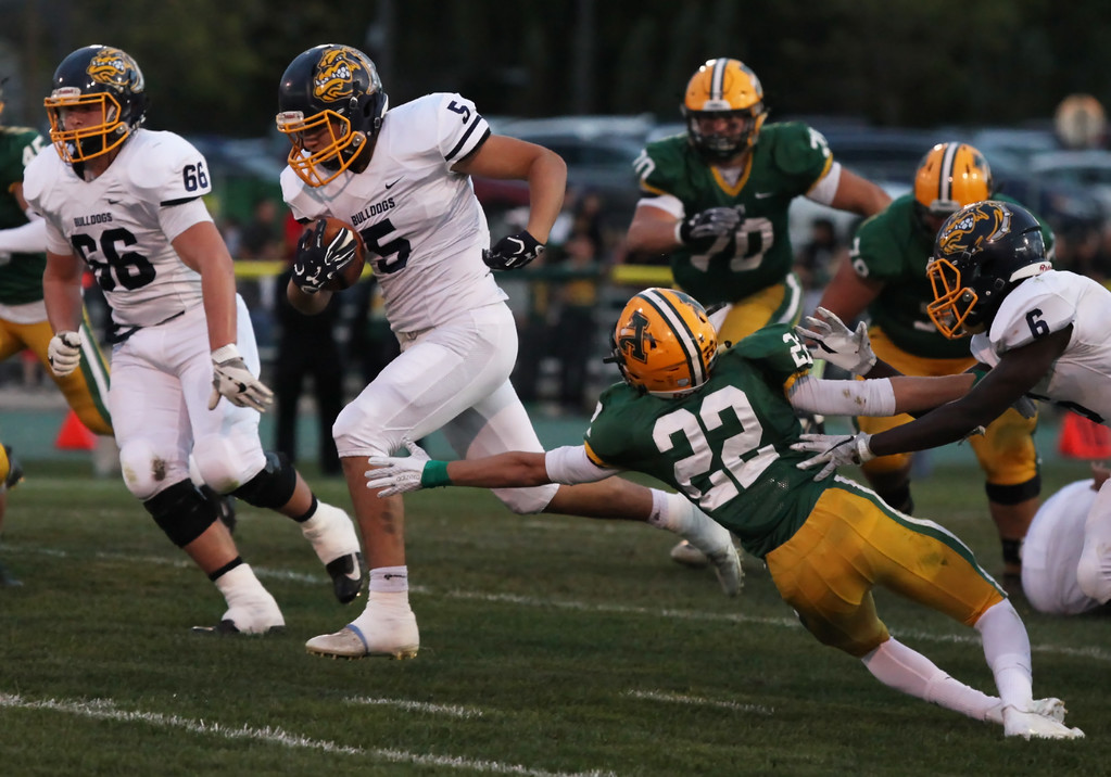 . Randy Meyers - The Morning Journal<br> Luke Lombardo of Olmsted Falls runs by Hunter Parker of Amherst for a big gain during the first quarter on Sept. 29.