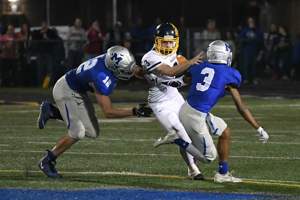 . Eric Bonzar�The Morning Journal<br> Olmsted Falls\' Nick Daily (3) looks to slice through Midview defenders Seth Frambach (12) and Aidan Breggins (3), Oct. 13, 2017.