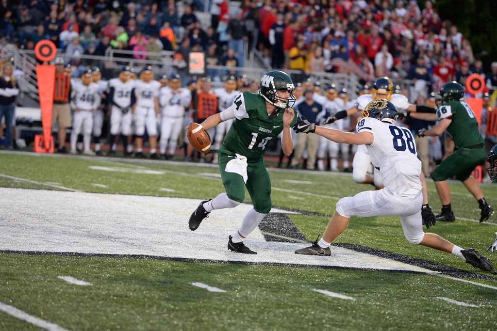 . Aimee Bielozer - The Morning Journal<br> Westlake quarterback Billy Blood tries to evade the sack attempt by Olmsted Falls\' Dylan Reines on Sept. 8.