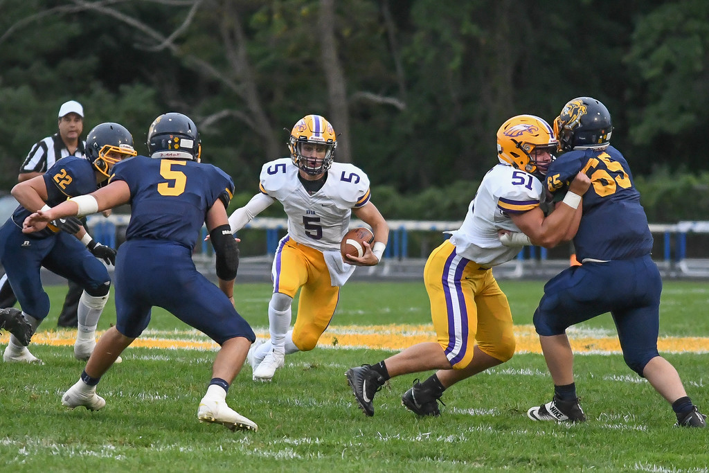 . Eric Bonzar�The Morning Journal<br> Avon Eagles quarterback Ryan Maloy (5) looks for a hole off a block by offensive lineman Jack Liber (51), Sept. 1, 2017.