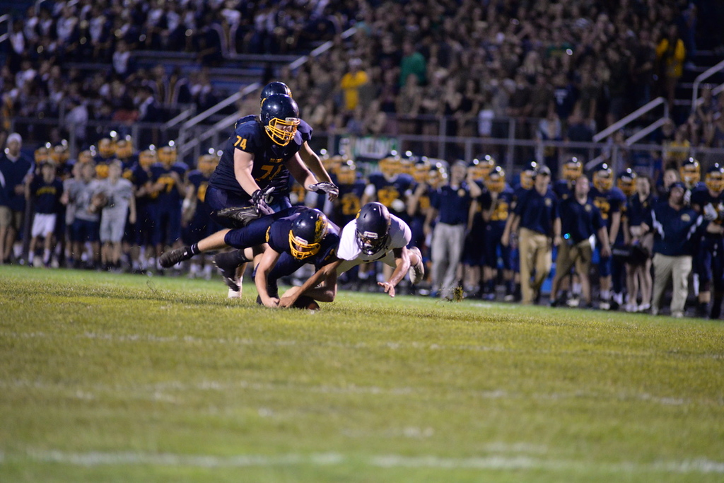 . Aimee Bielozer - The Morning Journal<br> North Ridgeville and Olmsted Falls players dive for a fumble on Sept. 22.