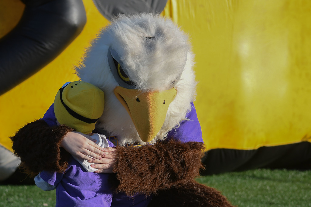. Eric Bonzar�The Morning Journal<br> A young fan gets a hug from Avon\'s Eagle mascot before the team\'s Southwestern Conference match-up against the Avon Lake Shoremen, Sept. 8, 2017.