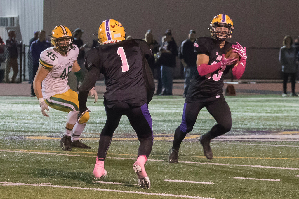. Jen Forbus - The Morning Journal<br> Avon\'s Evan Miller (13) secures an interception and heads up field against Amherst on Oct. 20.