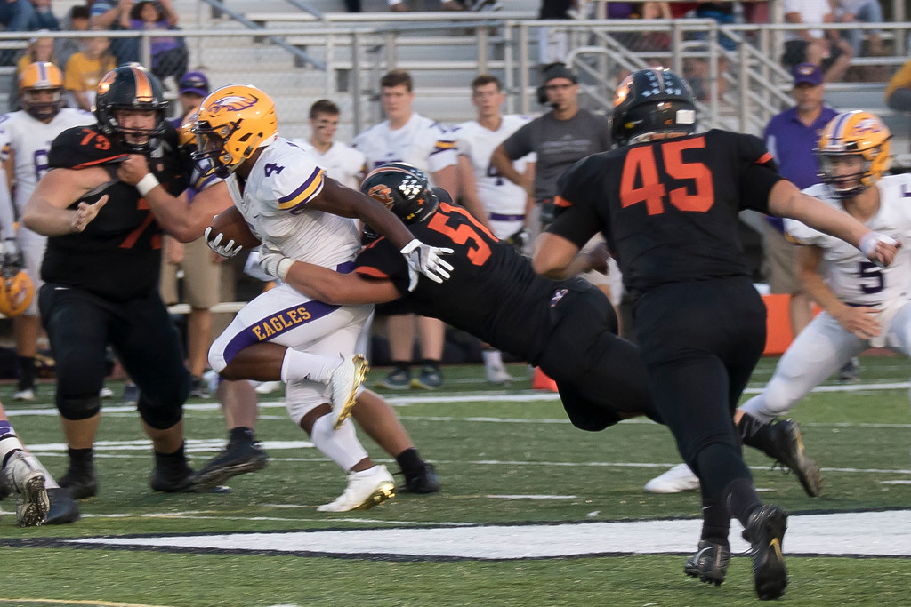 . Jen Forbus - The Morning Journal<br> Avon\'s Tony Eberhardt rushes forward as North Olmsted\'s Tyler Jones works to bring him down on Sept. 15.