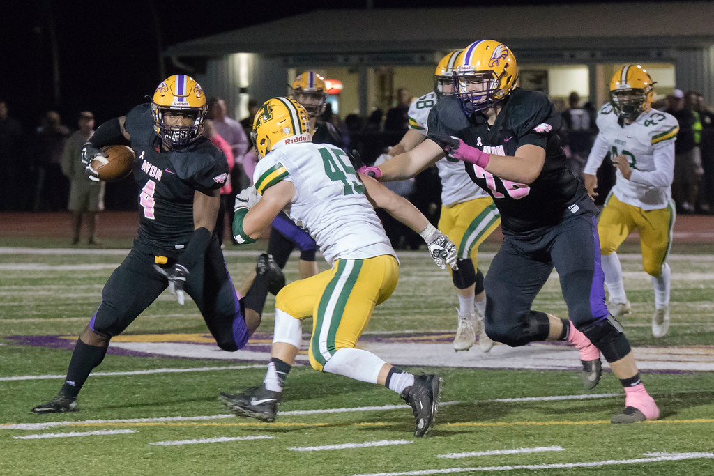 . Jen Forbus - The Morning Journal<br> Avon running back Tony Eberhardt (4) faces off with Amherst tight end Nathan Soto as Eagles\' tackle Michael Bergen (78) moves in to help on Oct. 20.