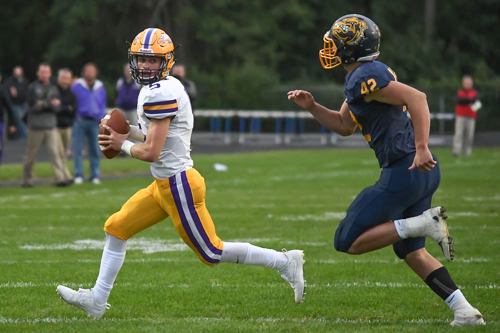 . Eric Bonzar�The Morning Journal<br> Avon Eagles quarterback Ryan Maloy (5) scrambles out of the pocket and looks for an open receiver with Olmsted Falls linebacker Jaden Mendeluk (42) chasing him down, Sept. 1, 2017.