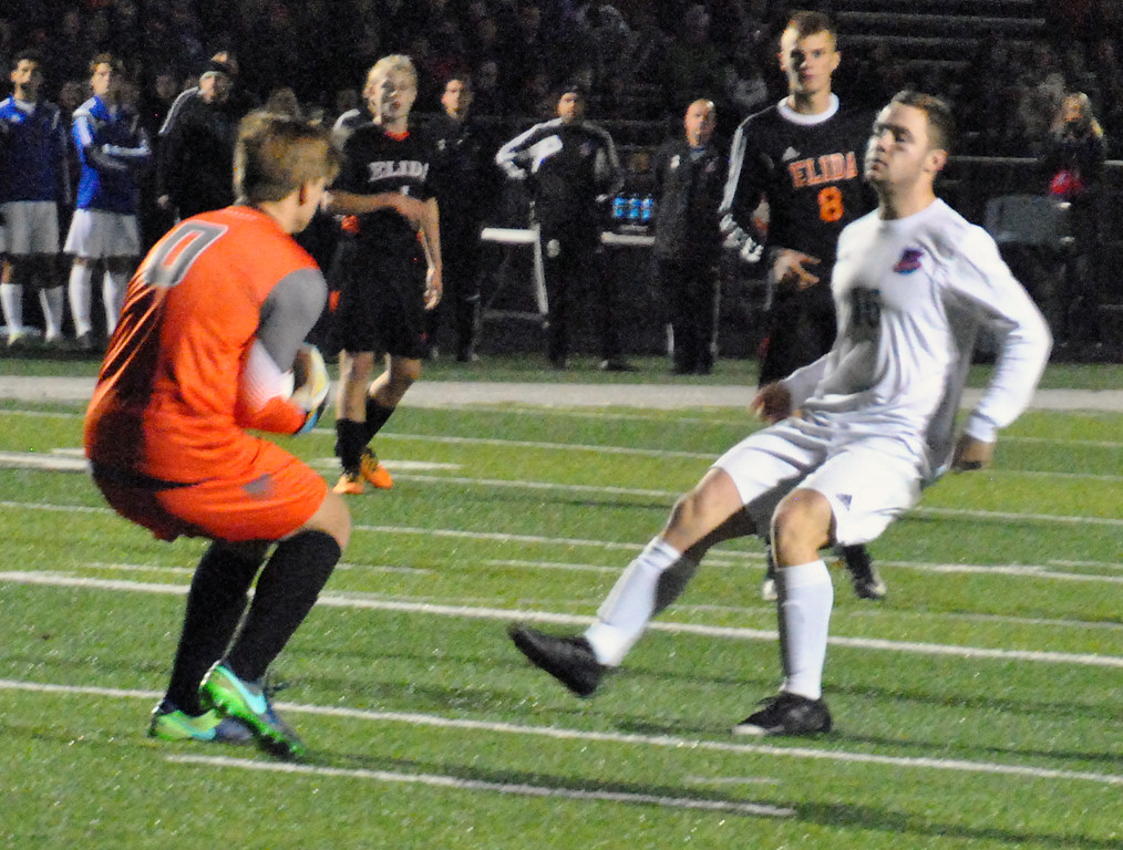 . Jon Behm - The Morning Journal<br> Elida goalkeeper Caleb Jones get the ball prior to Bay\'s Colin MacMillan during the second half on Nov. 4.