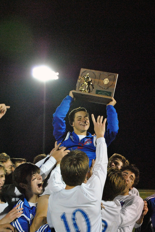 . Jon Behm - The Morning Journal<br> Sophomore midfielder Aidan Bozek shows off the regional championship trophy as he is lifted by his teammates following Bay\'s 4-1 victory over Elida in the Division II, Region 6 final on Nov. 4. The regional title is the 17th in the program\'s history.
