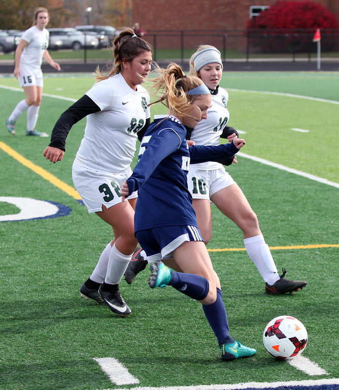 . Randy Meyers - The Morning Journal<br> Kirtland\'s Lilia Valentic kicks past Meredith Flanagan and Sadie Hutsenpillar of Elyria Catholic during the first half on Saturday