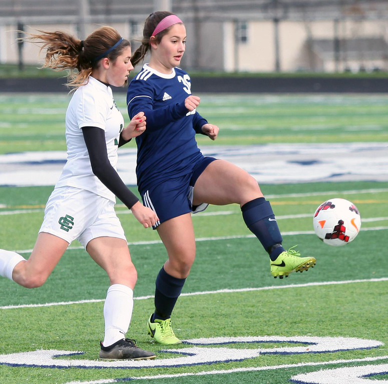 . Randy Meyers - The Morning Journal<br> Kirtland\'s Leah LaVerde kicks to a  teammate and past Avery Doll of Elyria Catholic during Saturday\'s regional final.