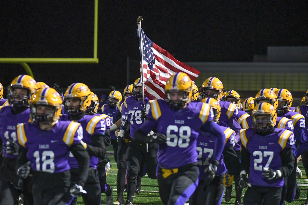 . Eric Bonzar�The Morning Journal<br> Avon\'s Michael Bergen (78) hoists the American flag as he and his teammates take the field against Medina Highland, Nov. 10, 2017.  The Eagles would go on to beat the Hornets, 28-10.
