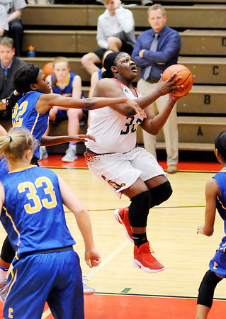 Don Knight | The Herald Bulletin<br /> Anderson's Kenigia Hamilton drives past Carmel's Tomi Taiwo for a basket at the Teepee on Wednesday.