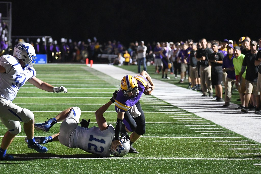 . Eric Bonzar�The Morning Journal<br> Avon quarterback Ryan Maloy (5) tumbles his way past Midview defensive lineman Seth Frambach (12), Sept. 22, 2017.
