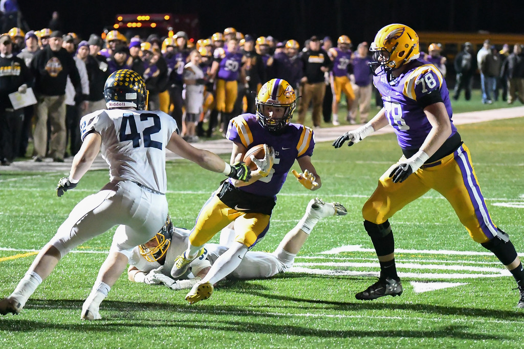. Eric Bonzar�The Morning Journal<br> Avon quarterback Ryan Maloy (5) cuts his way through a pair of Olmsted Falls defenders on his way to the end zone.