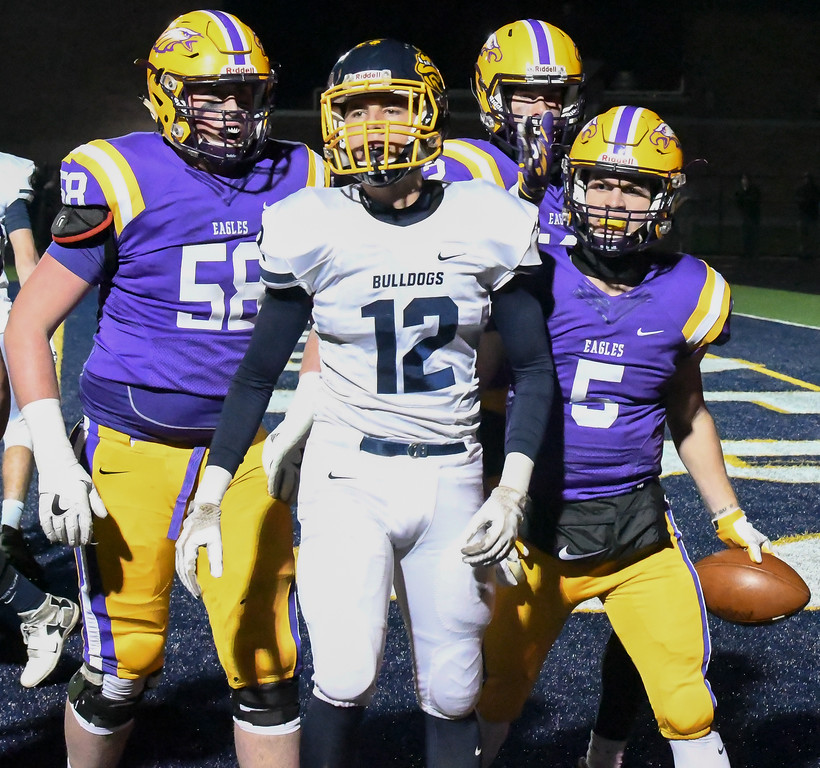 . Eric Bonzar�The Morning Journal<br> Olmsted Falls Michael Dulin (12) is surrounded by Eagles after quarterback Ryan Maloy (5) rushes in for a touchdown.