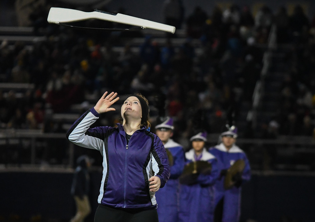 . Eric Bonzar�The Morning Journal<br> An Avon color guard member tosses her rifle in the air and catches it during the Eagles\' halftime performance.