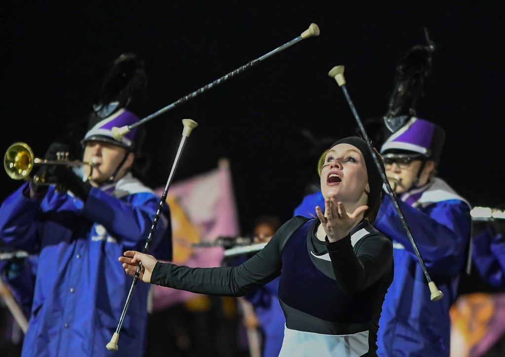 . Eric Bonzar�The Morning Journal<br> An Avon majorette juggles three batons during the Eagles\' halftime performance.