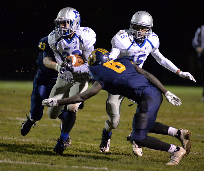 . Aimee Bielozer - The Morning Journal<br> Midview\'s Ben Gendics gets hit by Olmsted Falls\' Michael Howard (6) and Brian Eiseman on Nov. 3.