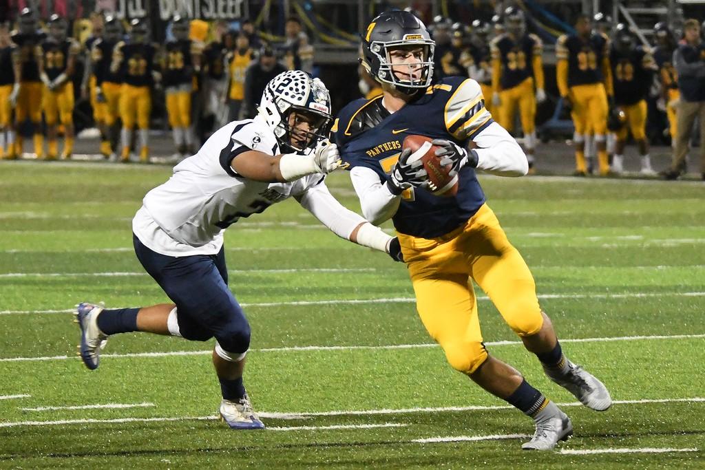 . Eric Bonzar�The Morning Journal<br> Toledo Whitmer quarterback Riley Keller (7) is grabbed by Lorain\'s Davion Dower (2).