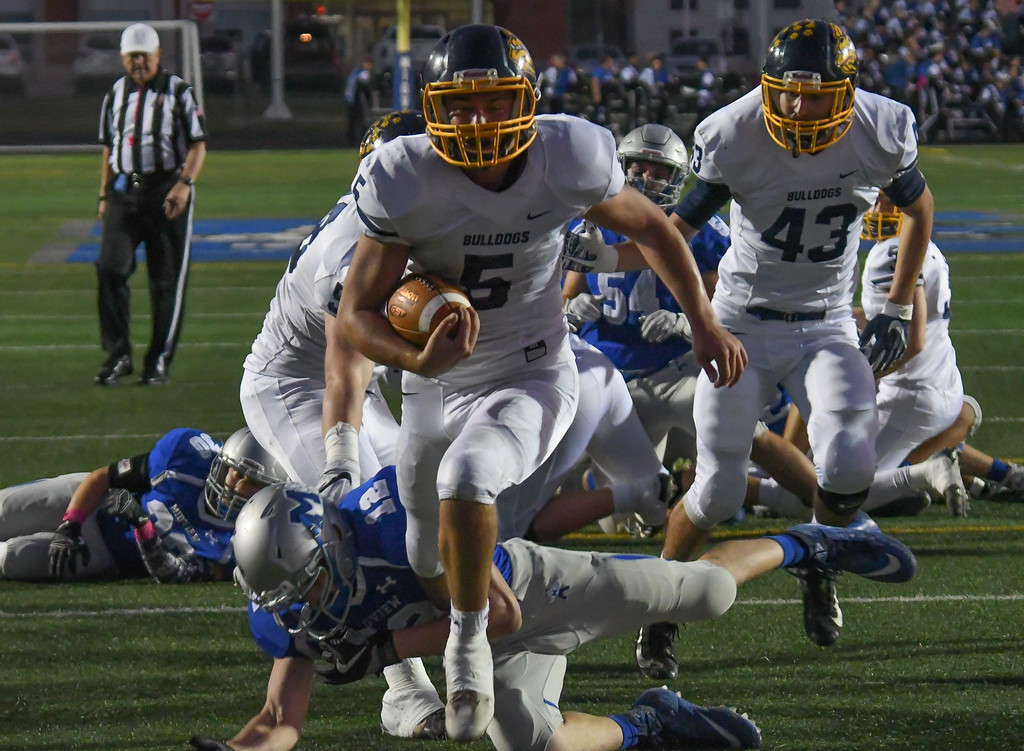 . Eric Bonzar�The Morning Journal<br> Olmsted Falls running back Luke Lombardo (5) punches it in to the end zone, giving the Bulldogs their first six points of the night, Oct. 13, 2017. Lombardo had three touchdowns on the night, in his team\'s 41-27 win over the Midview Middies.
