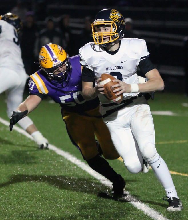 . Randy Meyers - The Morning Journal<br> Olmsted Falls quarterback Teddy Grendzynski rolls left and eludes the pass rush by Max Tolbert of Avon during the second quarter on Nov. 17.