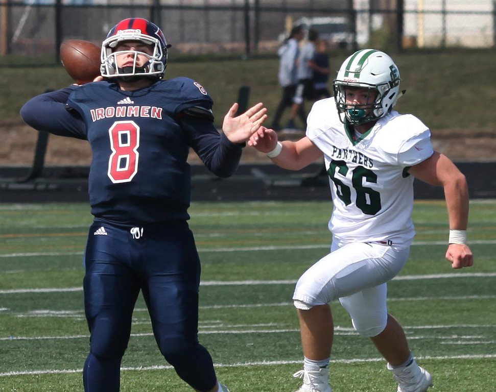 . Randy Meyers - The Morning Journal<br> Cleveland Central Catholic quarterback J.C. Dunn throws a deep ball despite the pass rush from Nick Pagenstecher of Elyria Catholic on Nov. 9.