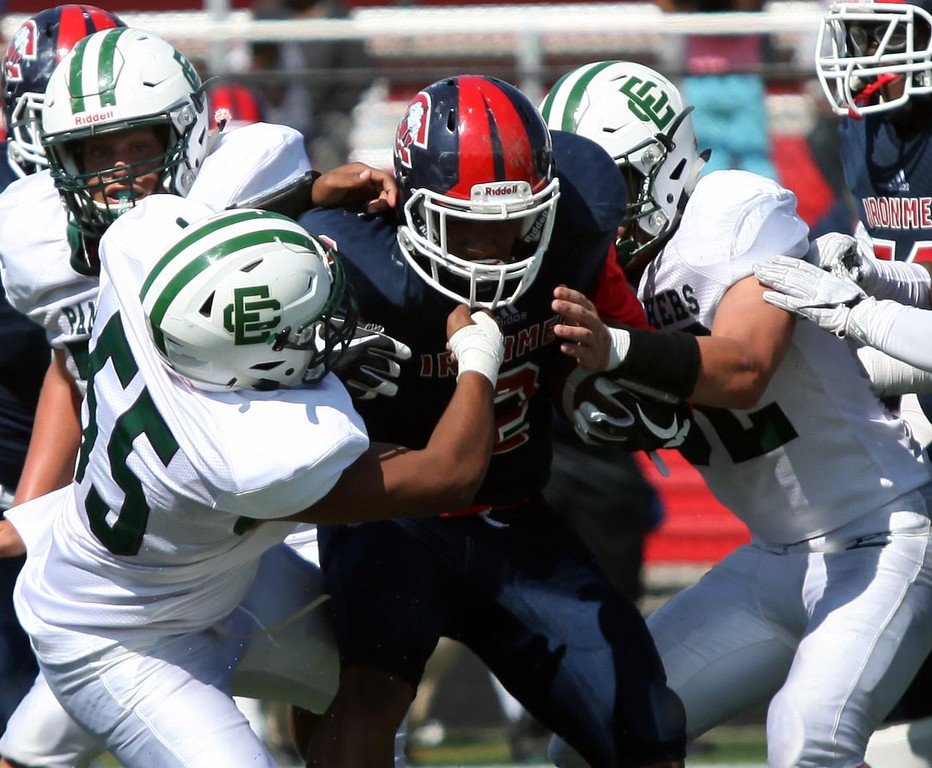 . Randy Meyers - The Morning Journal<br> Cleveland Central Catholic\'s Marvin Minger is stopped after a short gain by Javier Alvarez and Leighton Banjoff of Elyria Catholic during the fourth quarter on Sept. 9.