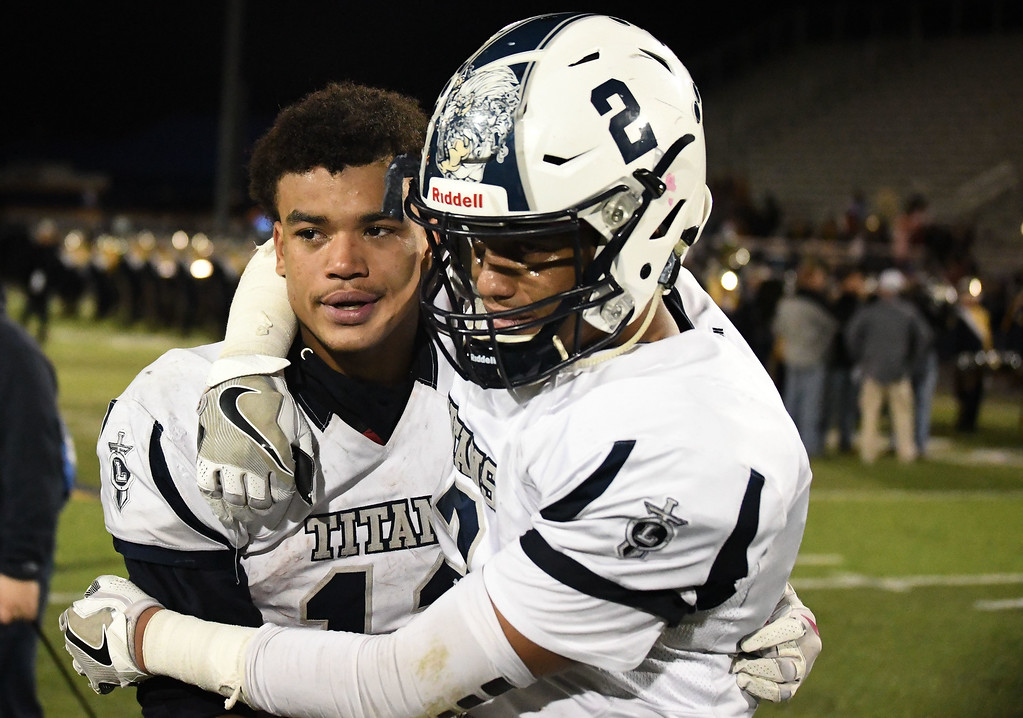 . Eric Bonzar�The Morning Journal<br> Brothers Daylin Dower (11) and Davion Dower (2) embrace as they walk off the field after a 31-28 loss to Toledo Whitmer. A last second field goal, as time expired, lifted the Panthers over the Titans.