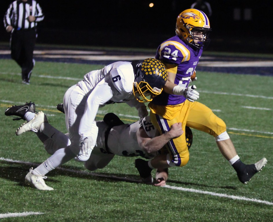 . Randy Meyers - The Morning Journal<br> Avon\'s Aaron Endrizal is brought down by Jack Spellacy and Michael Howard of Olmsted Falls on a kick return during the first quarter on Nov. 17.