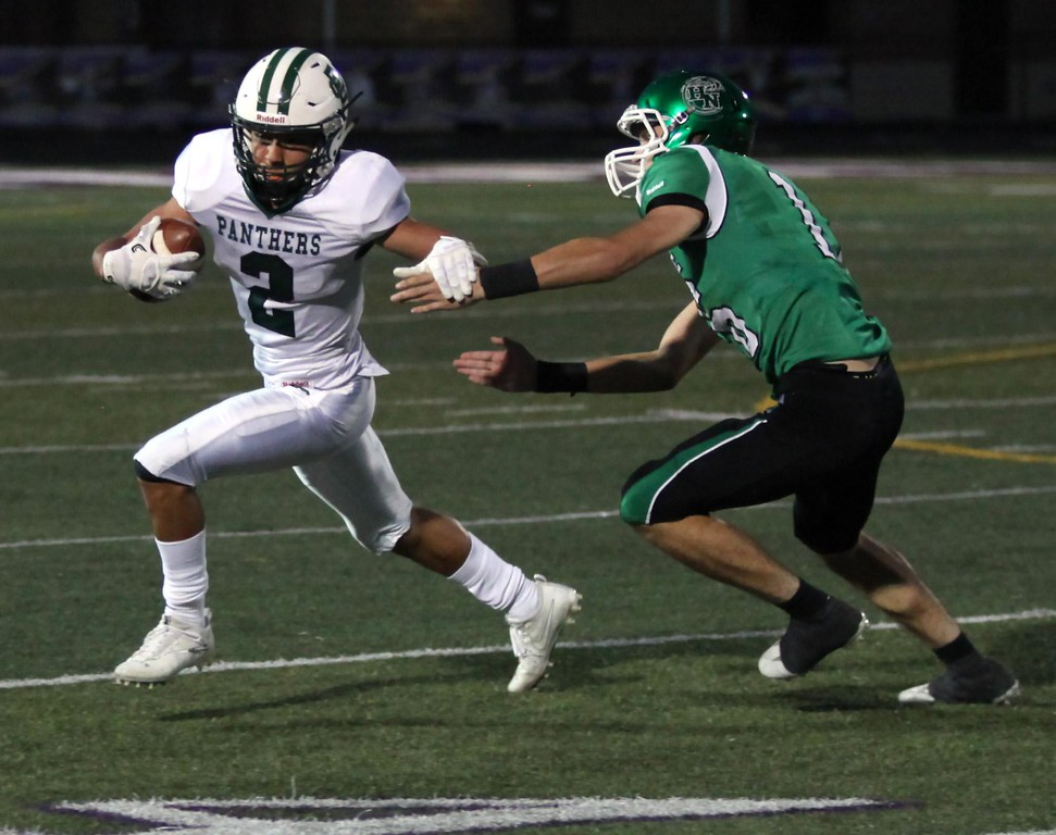 . Randy Meyers - The Morning Journal<br> Donovan Warfield of Elyria Catholic makes the catch and runs by Marques Thompson of Holy Name during the first quarter on Oct. 7.