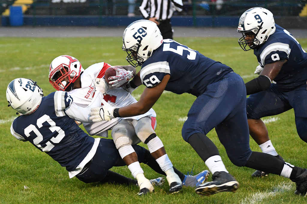 . Eric Bonzar�The Morning Journal<br> Elyria\'s Keshaun Glover (4) is brought down by Lorain defensive backs Jermele Nolen Jr. (23) and Myron Wilson (59), Sept. 7, 2017.