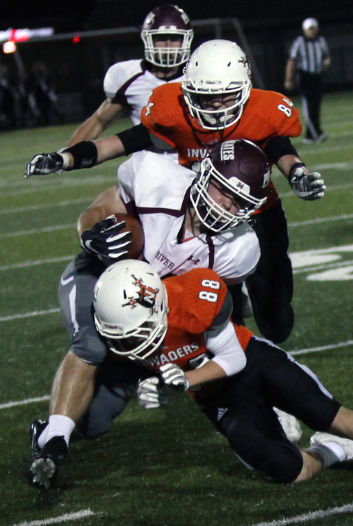 . Randy Meyers - The Morning Journal<br> Rocky River running back Matthew Popovich is brought down after a big gain during the first quarter by Corey Penny and Tommy Sullivan of Normandy on Oct. 12.