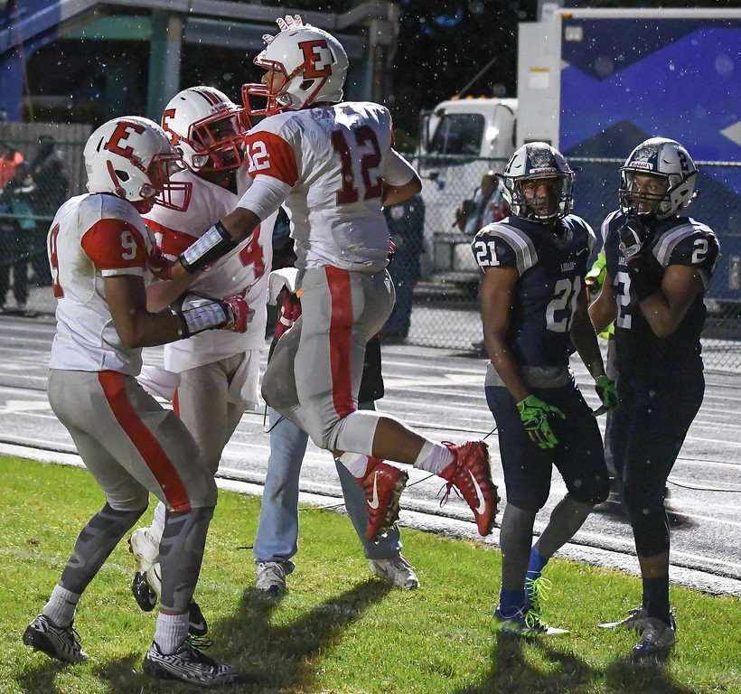 . Eric Bonzar�The Morning Journal<br> Elyria\'s Scott Ethington (12) celebrates a touchdown with teammates Izaiah Thomas (9) and Keshaun Glover (4), Sept. 7, 2017.