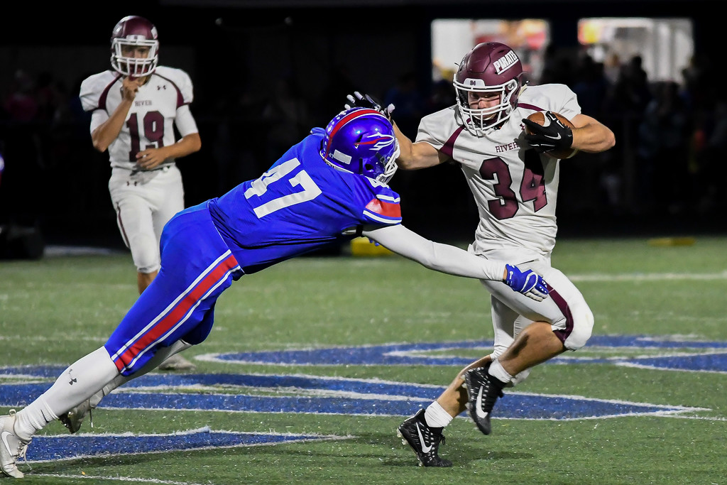 . Eric Bonzar�The Morning Journal <br> Rocky River\'s Matthew Popovich (34) stiff arms his way past Bay linebacker Vladimir Miskovic (47), Sept. 29, 2017.