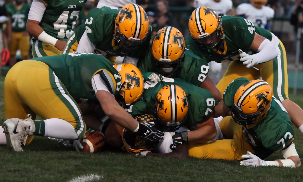 . Randy Meyers - The Morning Journal<br> Olmsted Falls running back Michael Howard is buried under six Amherst defenders during a first quarter run on Sept. 29.