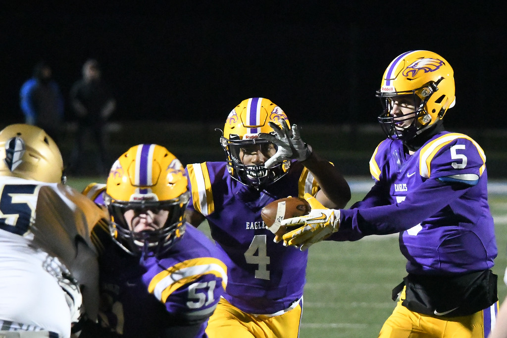. Eric Bonzar�The Morning Journal<br> Avon running back Tony Eberhardt (4) takes the hand-off from quarterback Ryan Maloy.